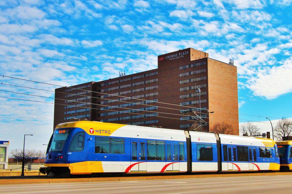 Picture of the Crowne Plaza at the Mall of America. The picture includes an image of a light rail in front.